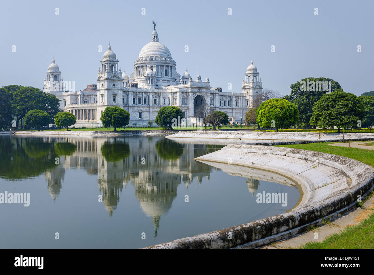 The Victoria Memorial on a bright sunny morning with blue sky with reflections of the memorial in the water, Kolkata, India. - Stock Image
