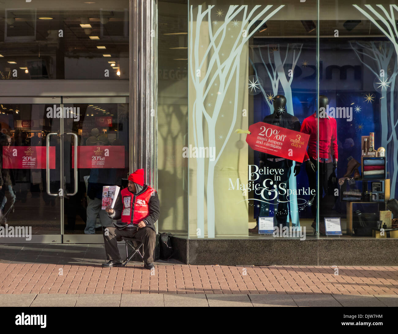 Big issue seller outside a department store.Optimistic, pessimistic. - Stock Image