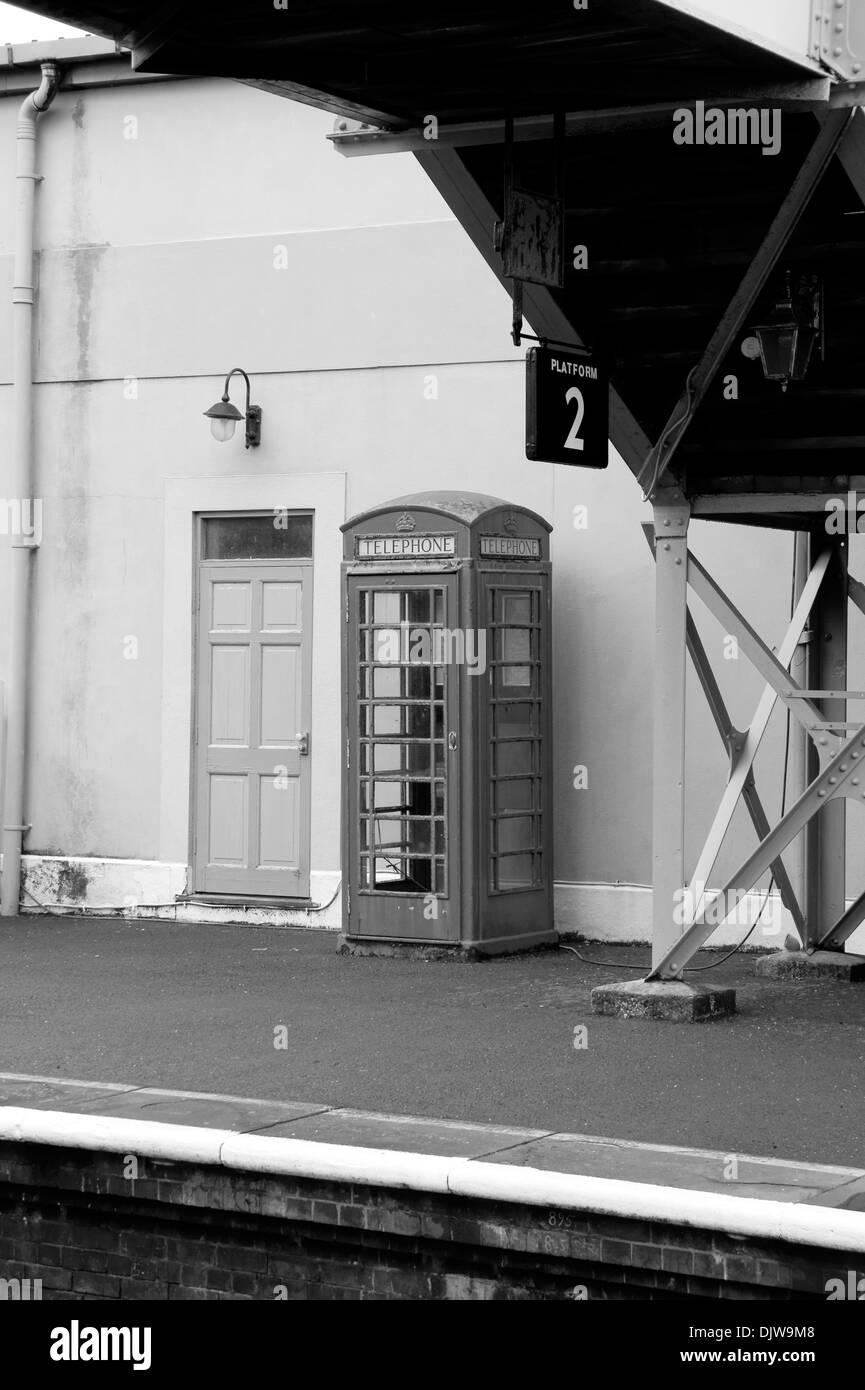 Black & White of Old Telephone Box on Platform 2 of Churston Railway Station, Devon, England. - Stock Image