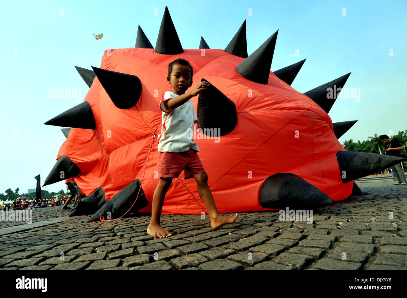 Jakarta, Indonesia. 1st Dec, 2013. A boy walks past a kite during the Jakarta International Kite Festival 2013 in Jakarta, Indonesia, Nov. 30, 2013. The two-day festival opened on Saturday, with the participation of 18 countries and regions. Credit:  Agung Kuncahya B./Xinhua/Alamy Live News Stock Photo