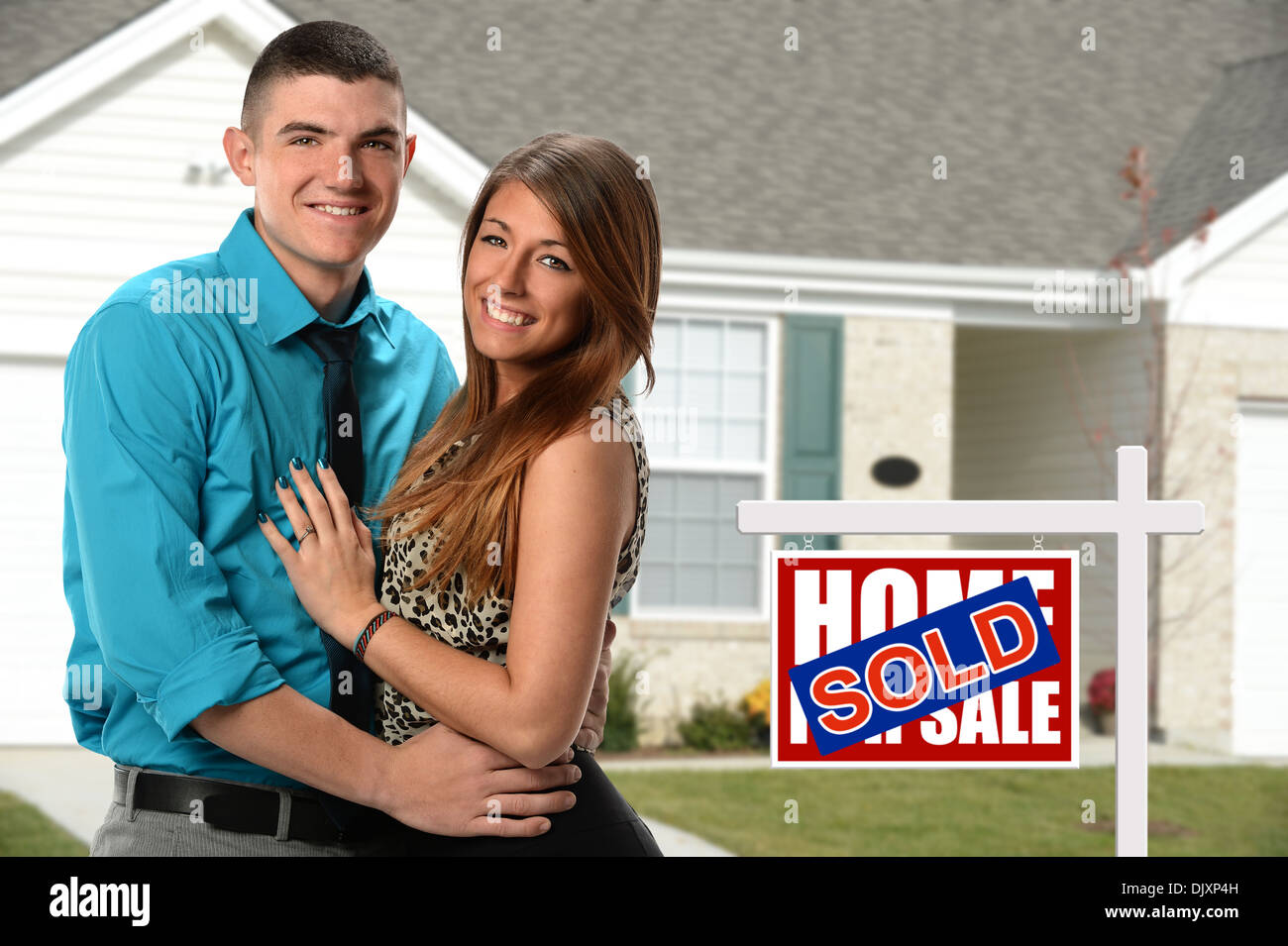 Happy young couple in front of newly sold home - Stock Image