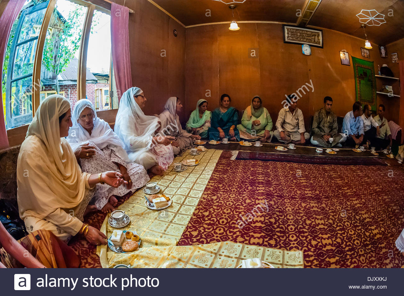 A Muslim engagement party where the bride and grooms families meet, in a houseboat on Dal Lake, Srinagar, Kashmir, - Stock Image