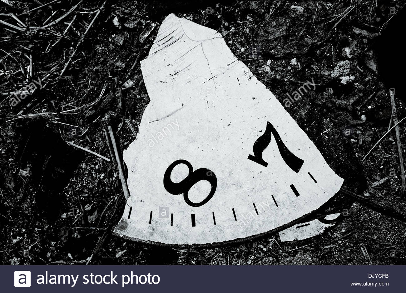 A fragment of a clock face numbers '8' and '7' lies abandoned in the edgelands surrounding the South Korean city of Chungju. - Stock Image