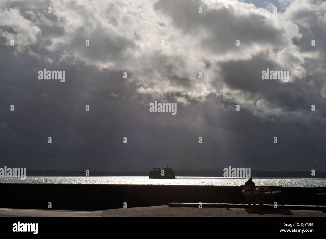 A solitary person watches the approaching storm at Southsea, Portsmouth. - Stock Image
