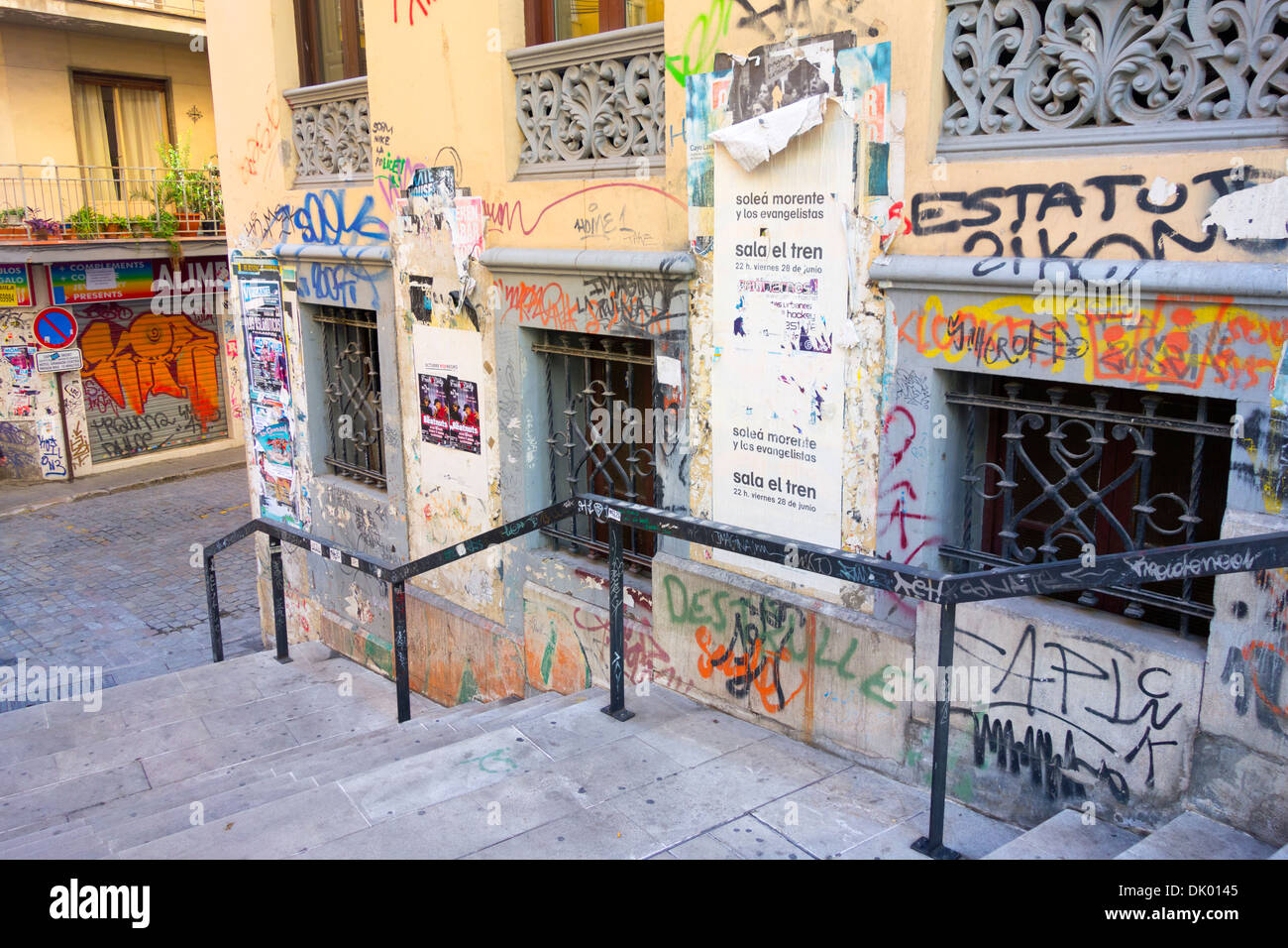 Wall covered in graffiti and fly posting just outside of the main city centre area in Granada Spain - Stock Image