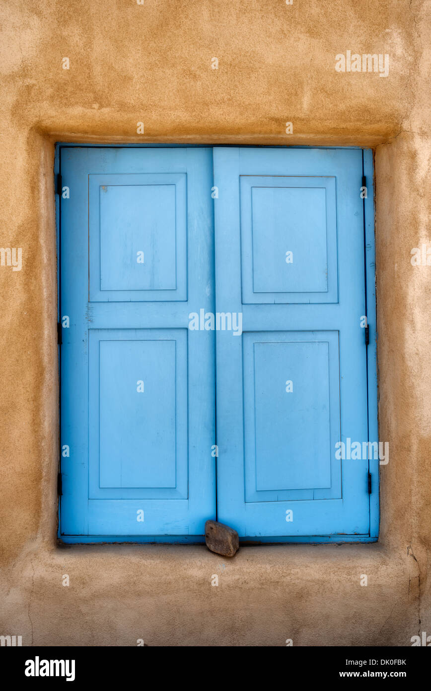 Window with rock closure and adobe wall. Taos, NM - Stock Image