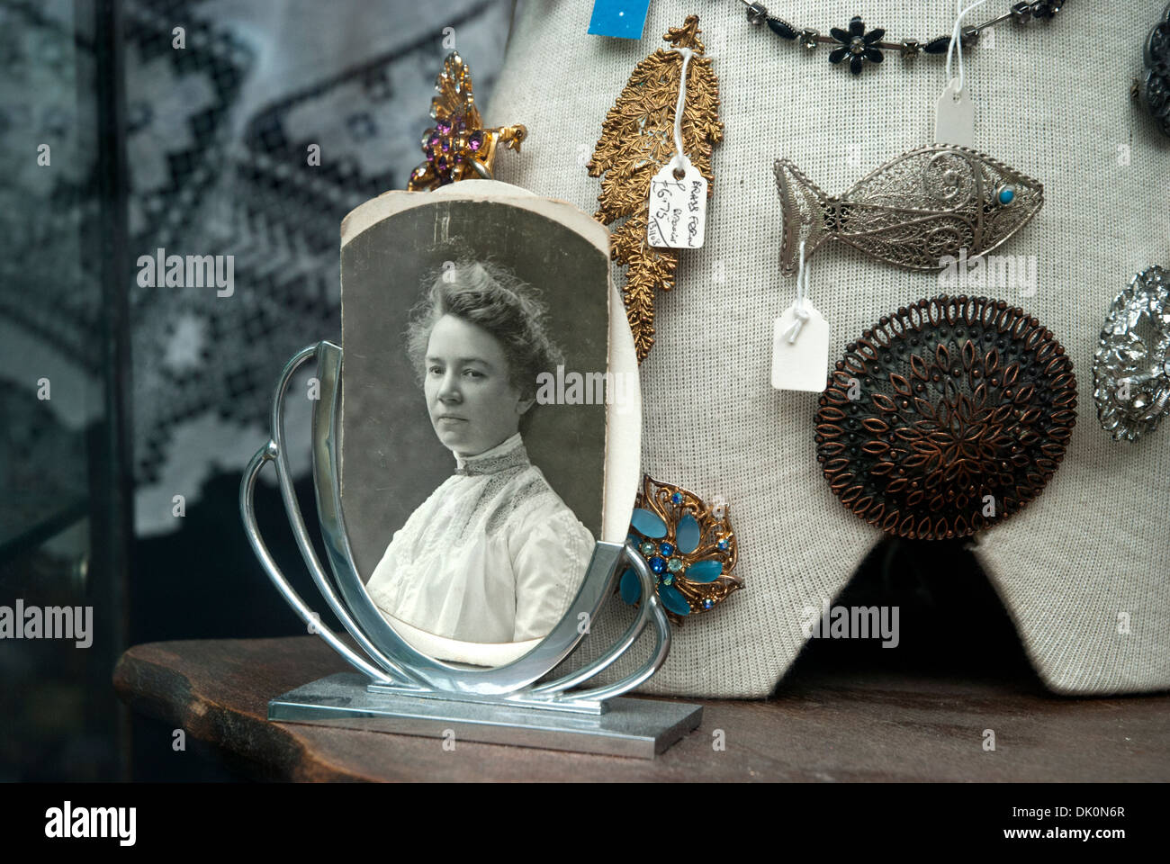 Black and white photograph of a Victorian woman on display in an antique/junk shop window. - Stock Image