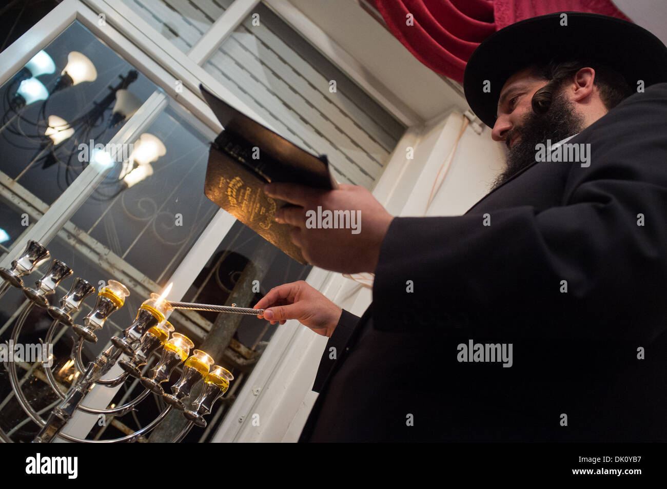 Sanhedria, Jerusalem, Israel. 1st Dec 2013. Yaacov Yeruslavski, a Breslov Hassidic, ultra-Orthodox, Jewish man, lights five candles on the eight-branched menorah with his family in their home in the Orthodox neighborhood of Sanhedria, celebrating the fifth night of Hanukkah. Jerusalem, Israel. 1-Dec-2013.   The Breslov Hassidic, ultra-Orthodox, Yeruslavski family, light five candles on the eight-branched menorah celebrating the fifth night of Hanukkah, commemorating the oil lamp that miraculously burned for eight days in the destroyed Temple in 164 BCE. Credit:  Nir Alon/Alamy Live News - Stock Image