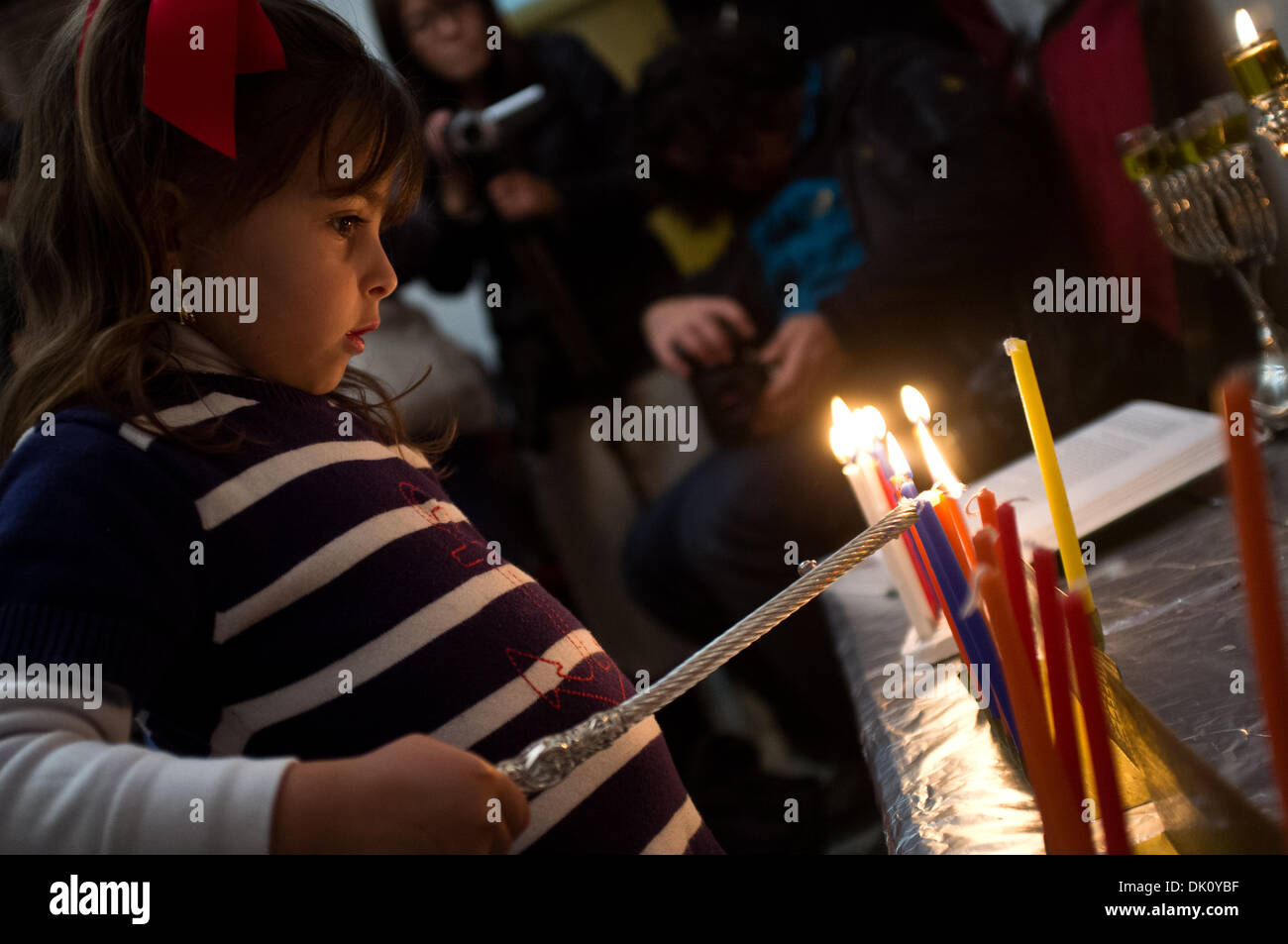Sanhedria, Jerusalem, Israel. 1st Dec 2013. A young girl lights five candles on the eight-branched menorah with her family, belonging to the Breslov Hassidic, ultra-Orthodox community, in her home in the Orthodox neighborhood of Sanhedria. Jerusalem, Israel. 1-Dec-2013.   The Breslov Hassidic, ultra-Orthodox, Yeruslavski family, light five candles on the eight-branched menorah celebrating the fifth night of Hanukkah, commemorating the oil lamp that miraculously burned for eight days in the destroyed Temple in 164 BCE. Credit:  Nir Alon/Alamy Live News - Stock Image