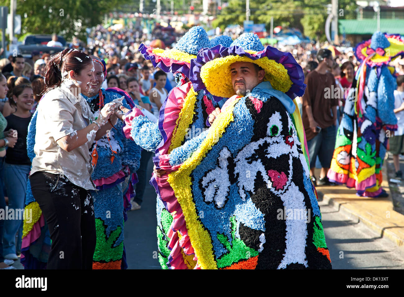 Woman covered in shaving cream, man in costume and crowd, Hatillo Mask Festival, Hatillo, Puerto Rico - Stock Image