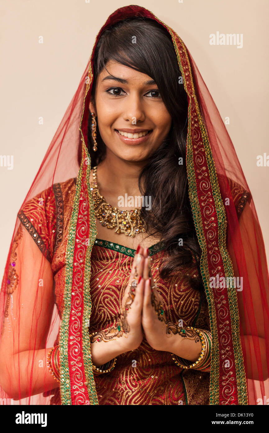 Portrait of a beautiful Indian woman dressed in traditional clothing holding hands in Namaste gesture. - Stock Image
