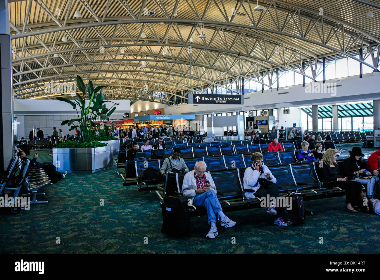 People in the departure lounge at Tampa Airport waiting for their flights - Stock Image