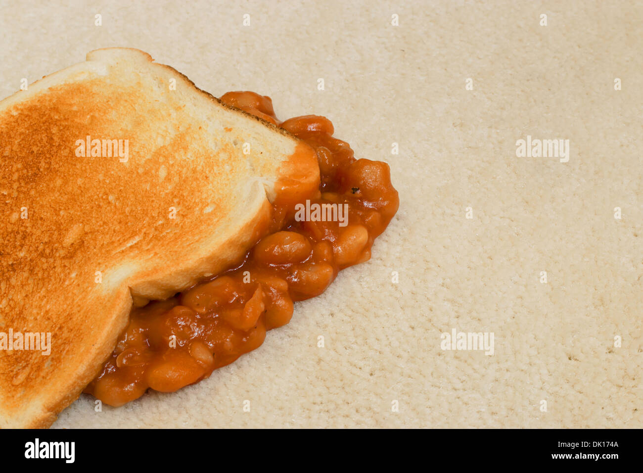 Baked Beans on toast accidentally dropped and creating a carpet stain on beige pile floor covering - Stock Image