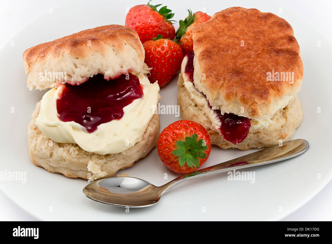 Traditional Afternoon Tea of Devonshire scones topped with clotted cream and strawberry jam often served with coffee or tea - Stock Image