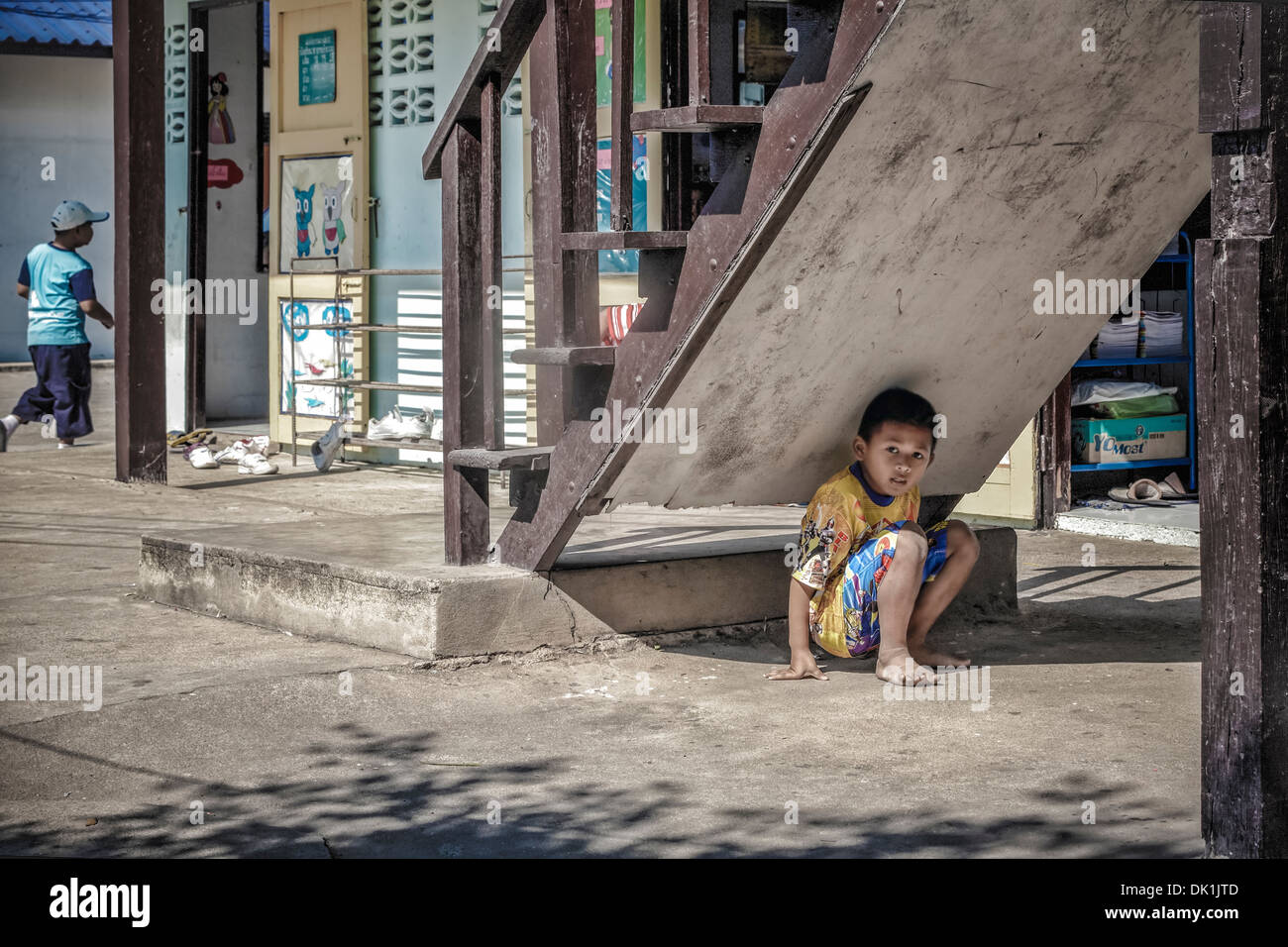 Young boys playing hide and seek in the school playground. Thailand S. E. Asia - Stock Image