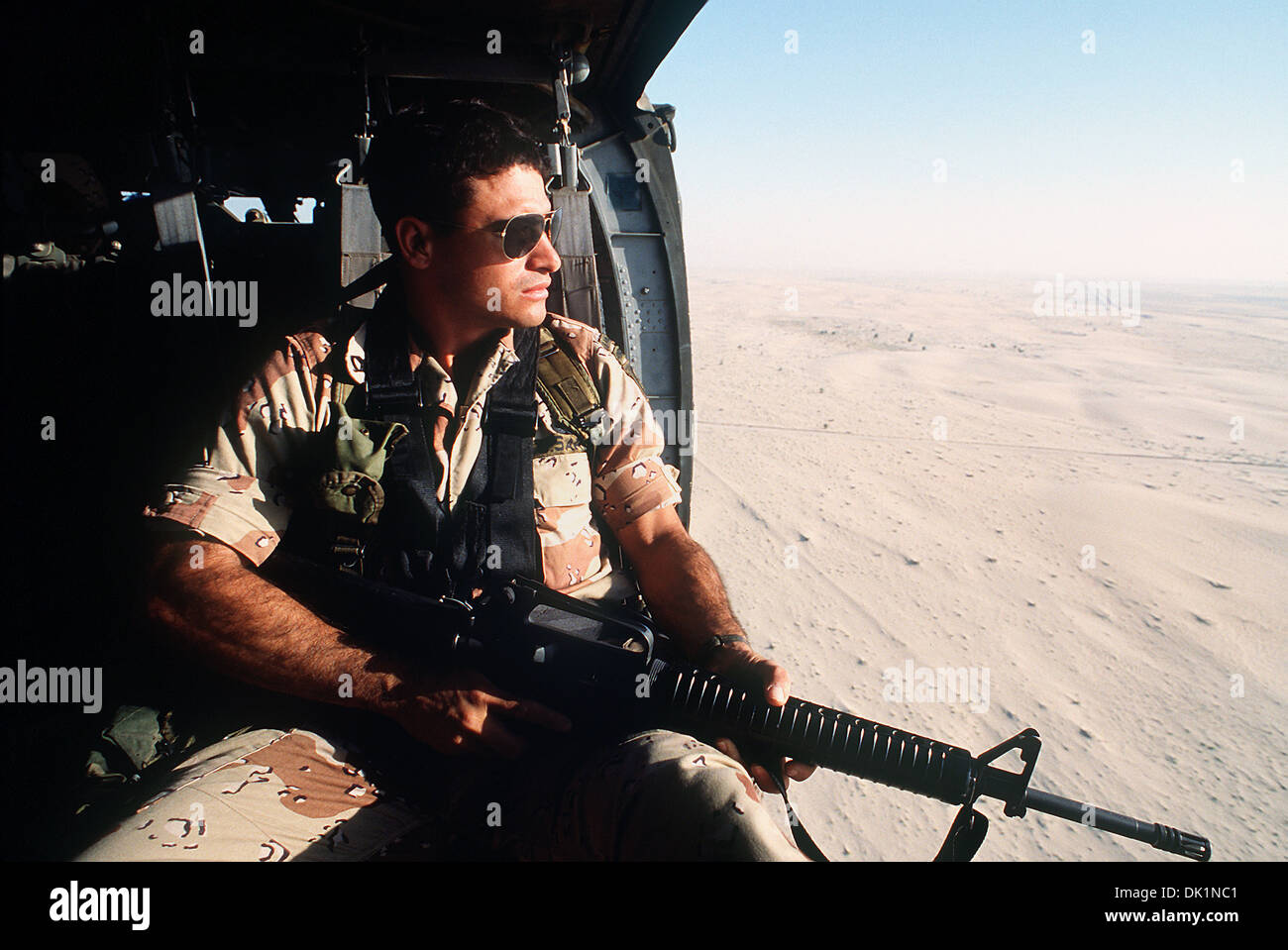 A US Army soldier keeps watch from a Black Hawk helicopter over the desert February 22, 1991 in Saudi Arabia. - Stock Image