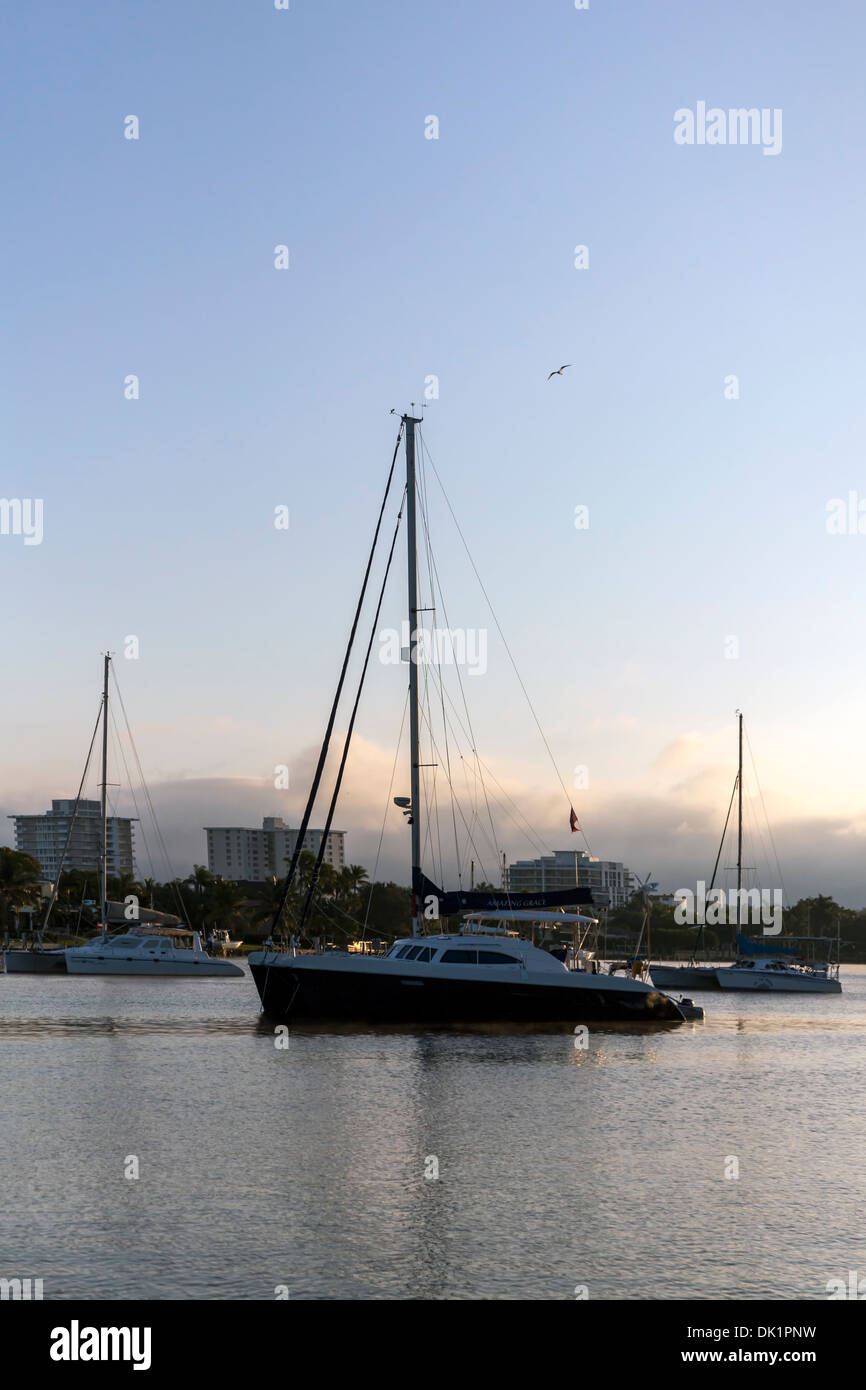 Sailboats anchored at sunrise in a sheltered anchorage along Middle River off Intracoastal Waterway in Fort Lauderdale, Florida. - Stock Image