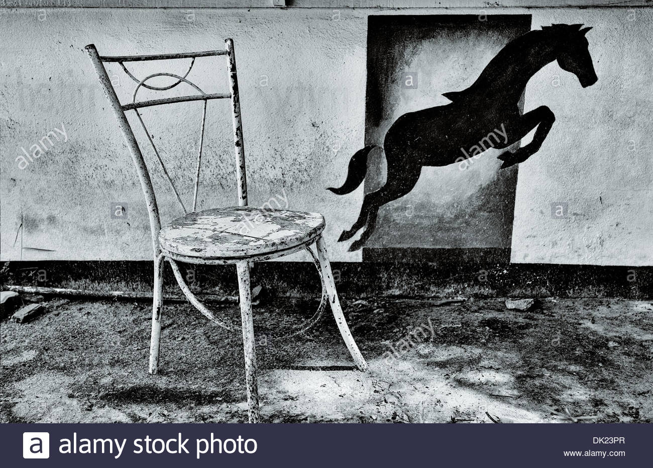 A painted horse appears to be leaping off an old metal chair in front of a derelict restaurant on the shore of Sangthain Beach. - Stock Image