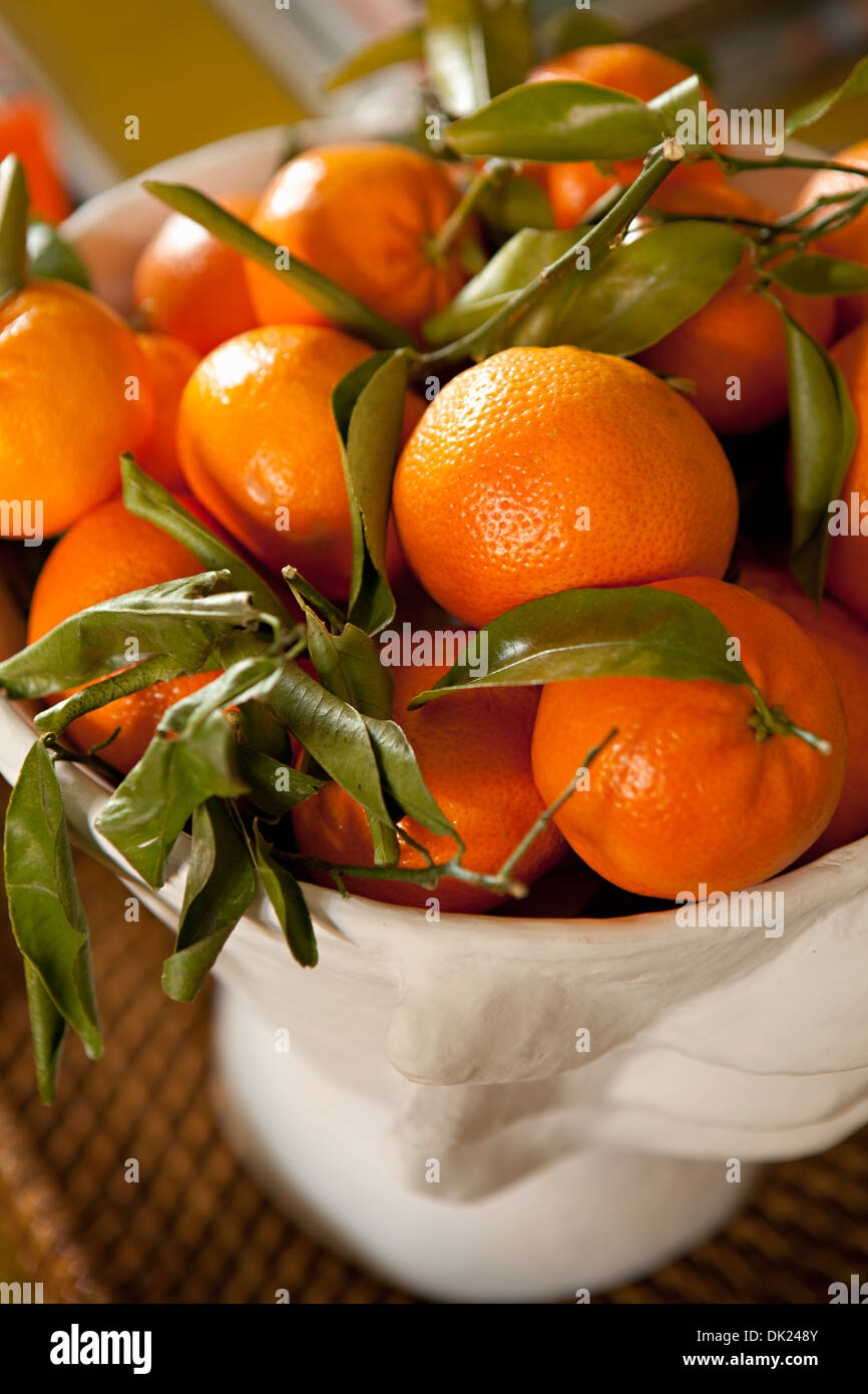 Close up high angle view of ripe orange tangerines in bowl - Stock Image