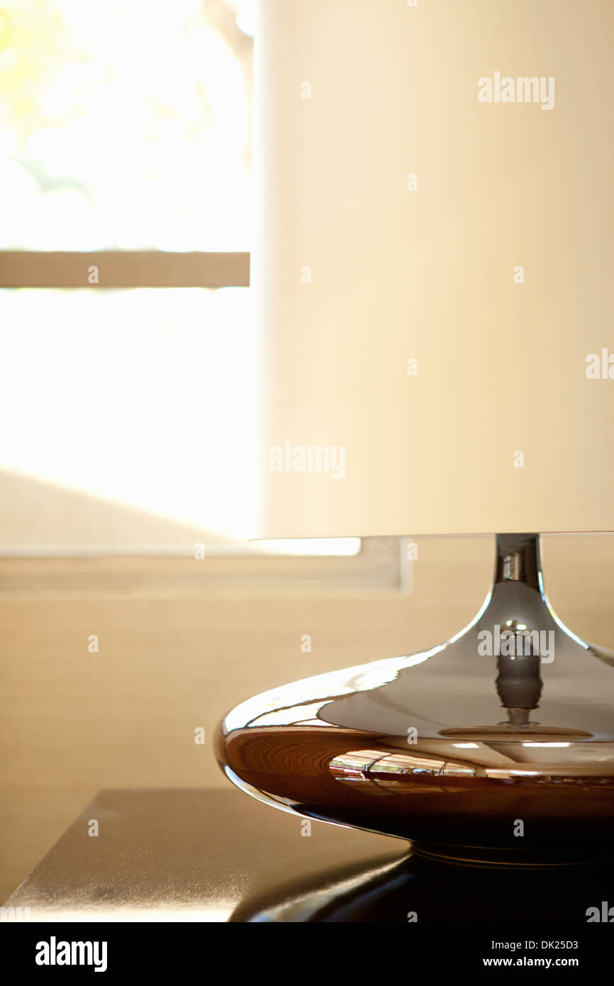 Close up of modern lamp with white lampshade on table by window - Stock Image