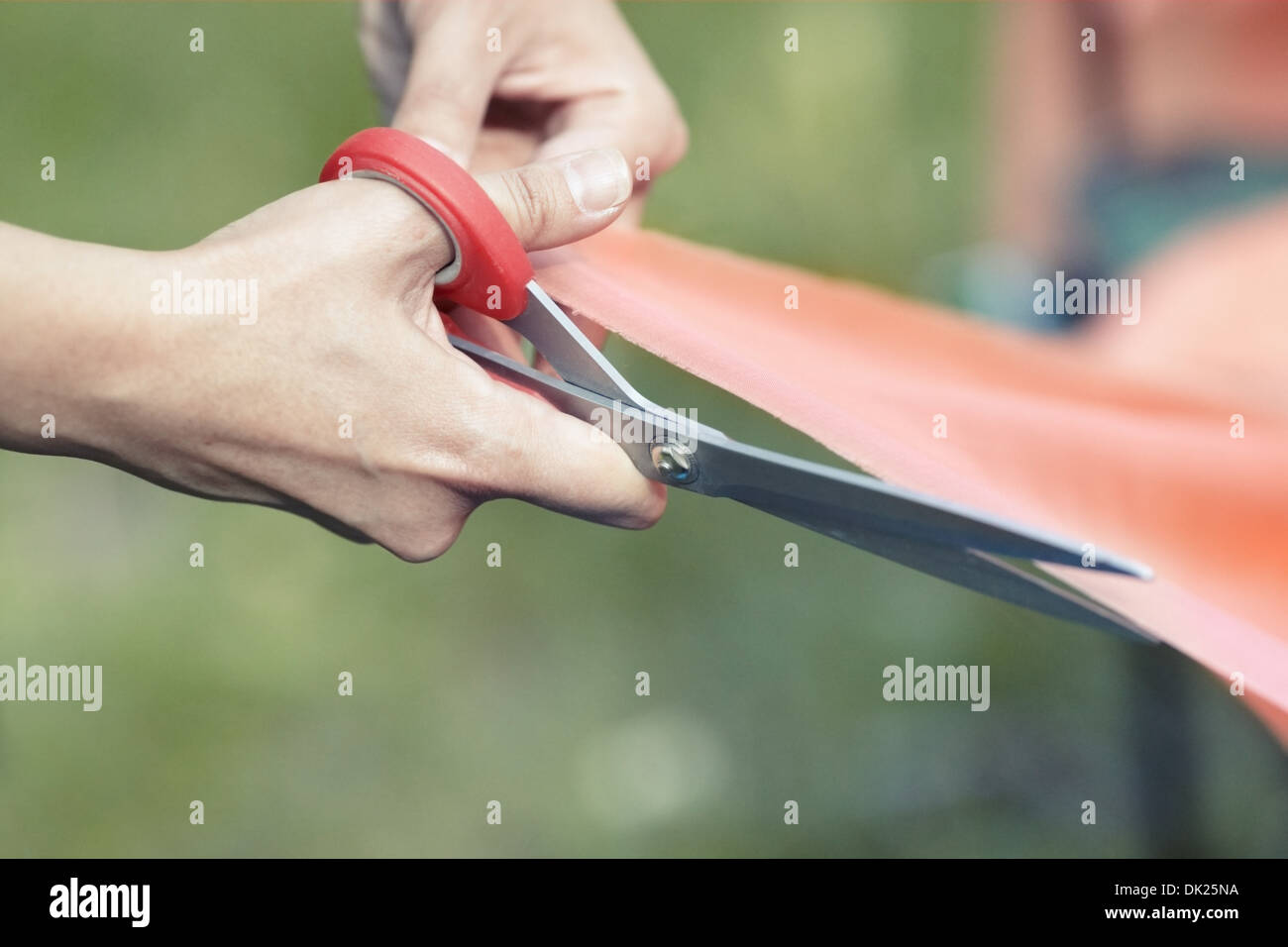 Hands of female tailor cutting red ribbon. Close-up view - Stock Image