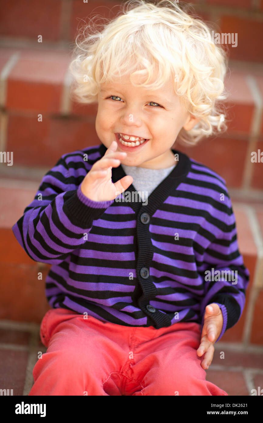 Close Up Of Tilt Blonde Toddler Boy With Curly Hair
