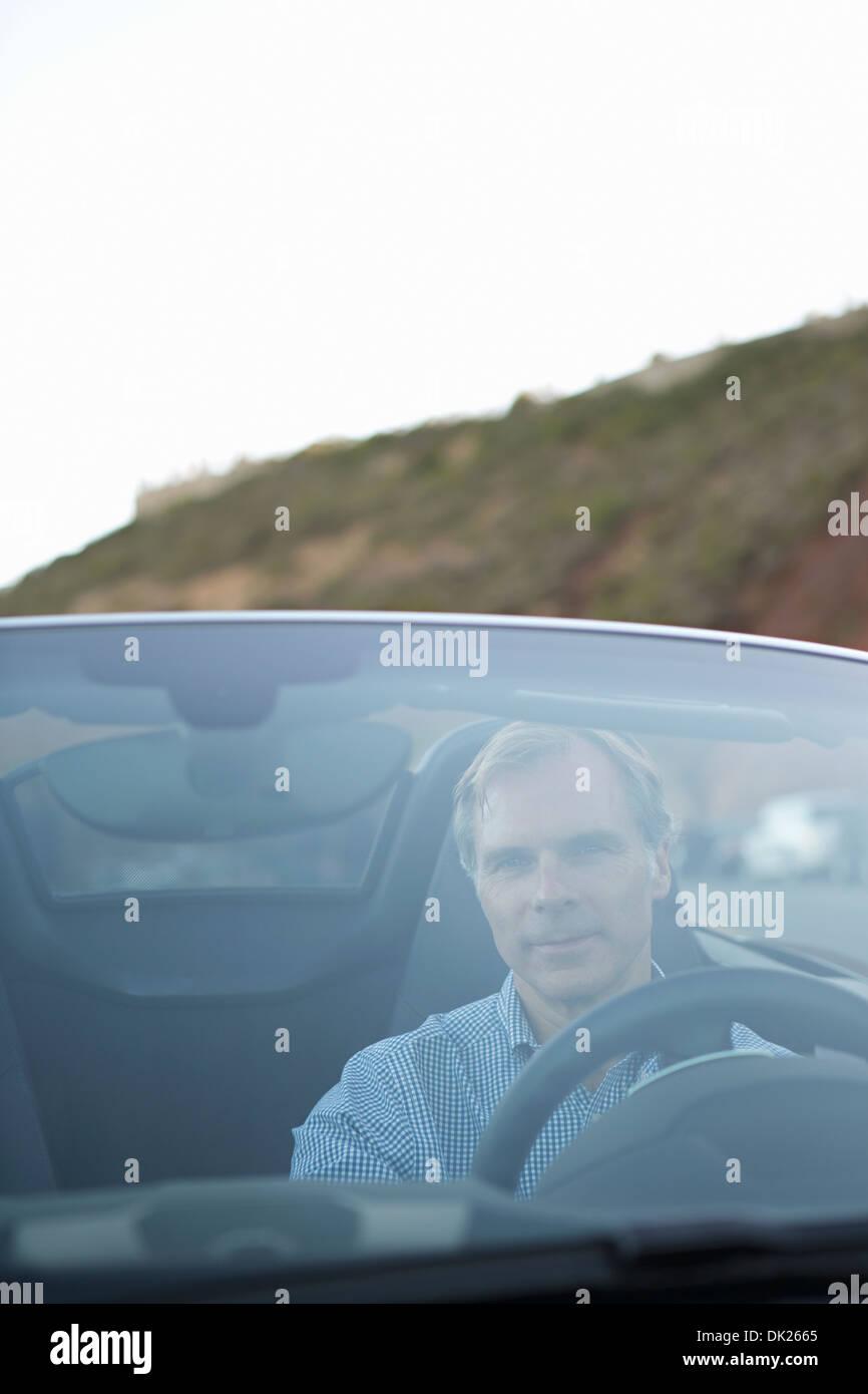 Man driving convertible sports car - Stock Image