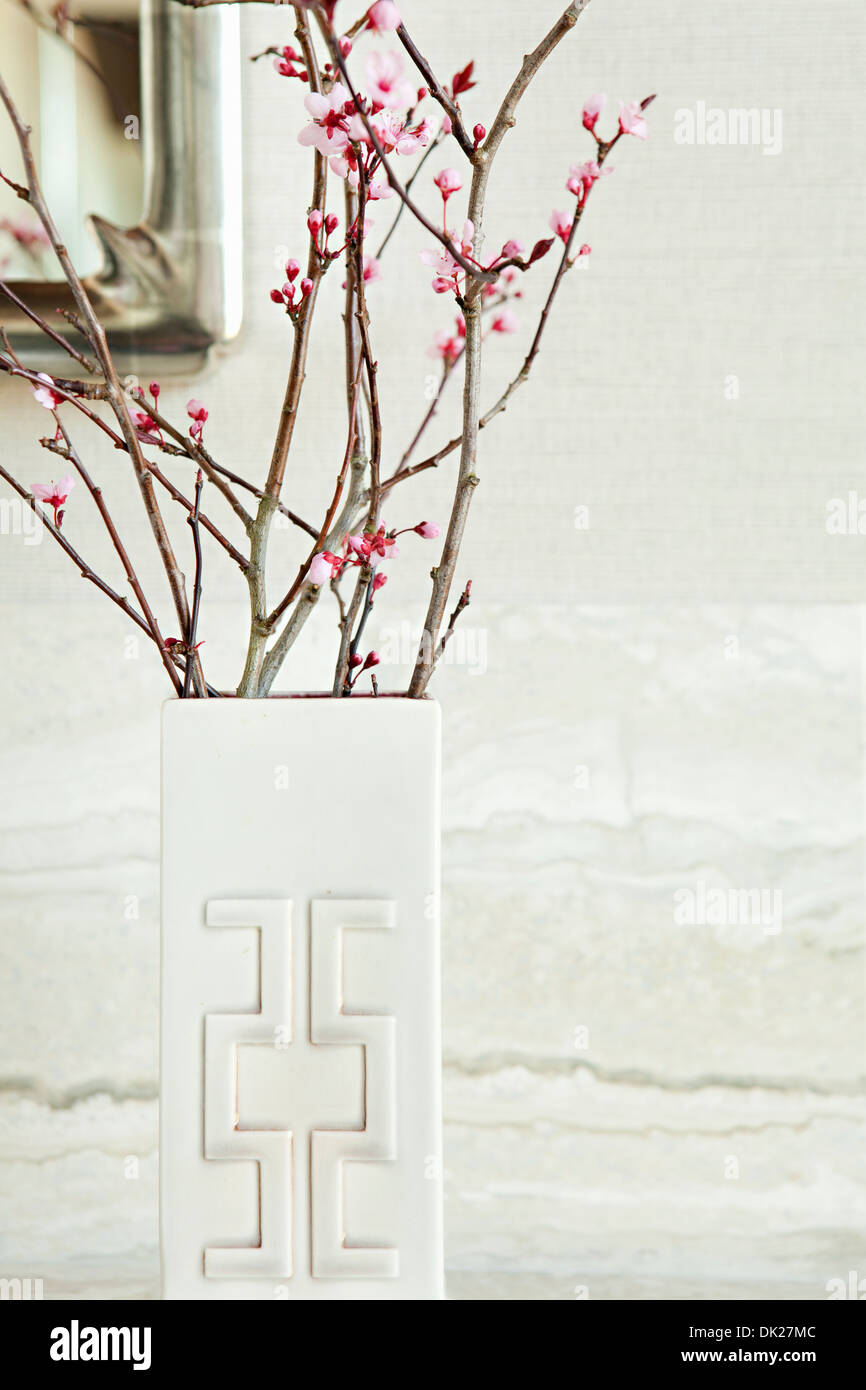 Close up of pink blossoms on twigs in modern white vase - Stock Image