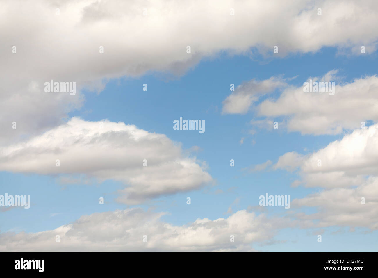 Fluffy white clouds in sunny blue sky - Stock Image