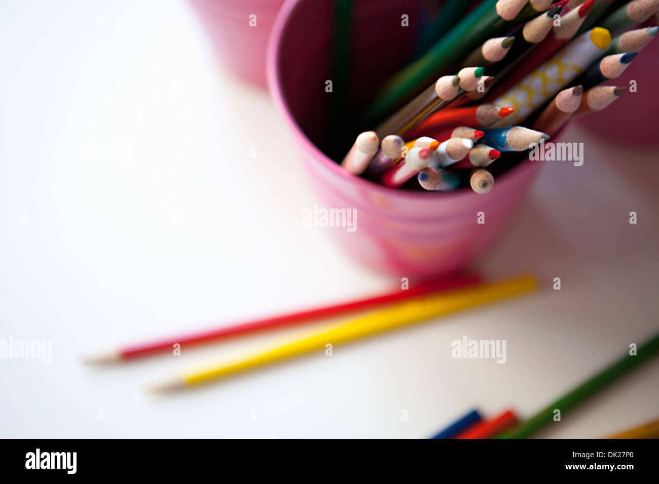 High angle view of multicolor art colored pencils in pink bucket - Stock Image