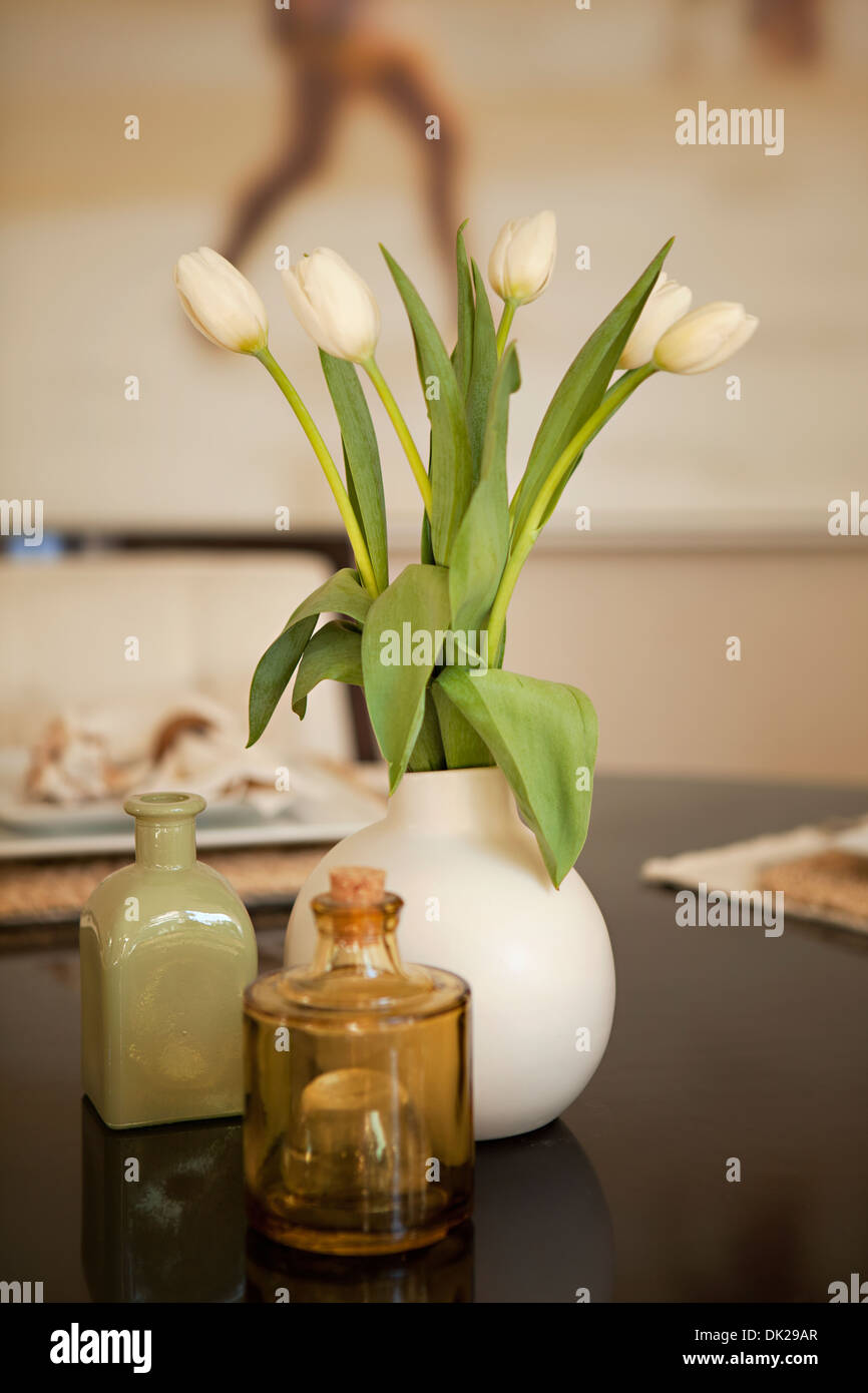 White tulips in vase on dining table - Stock Image