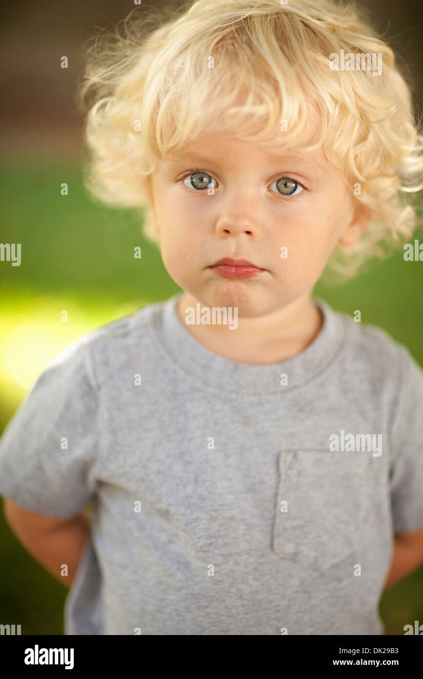 3e62cab89f5 Close up portrait of innocent blonde toddler boy with curly hair in gray  t-shirt