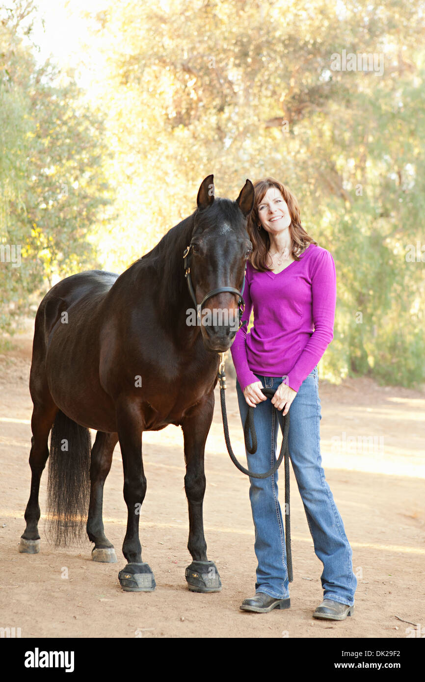 Portrait of smiling brunette woman in purple sweater with brown horse on dirt path - Stock Image