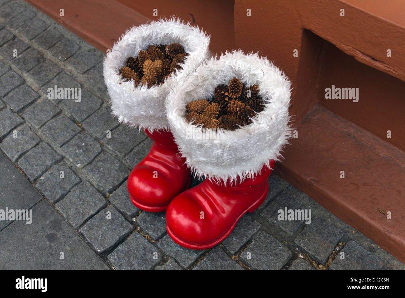 Santa's red boots filled with pine cones left outside a Christmas shop in Reykjavik, Iceland - Stock Image