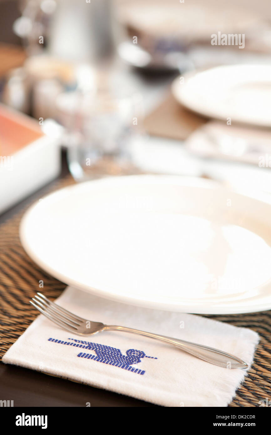 Close up of place settings and stitched Guatemalan napkin on table - Stock Image