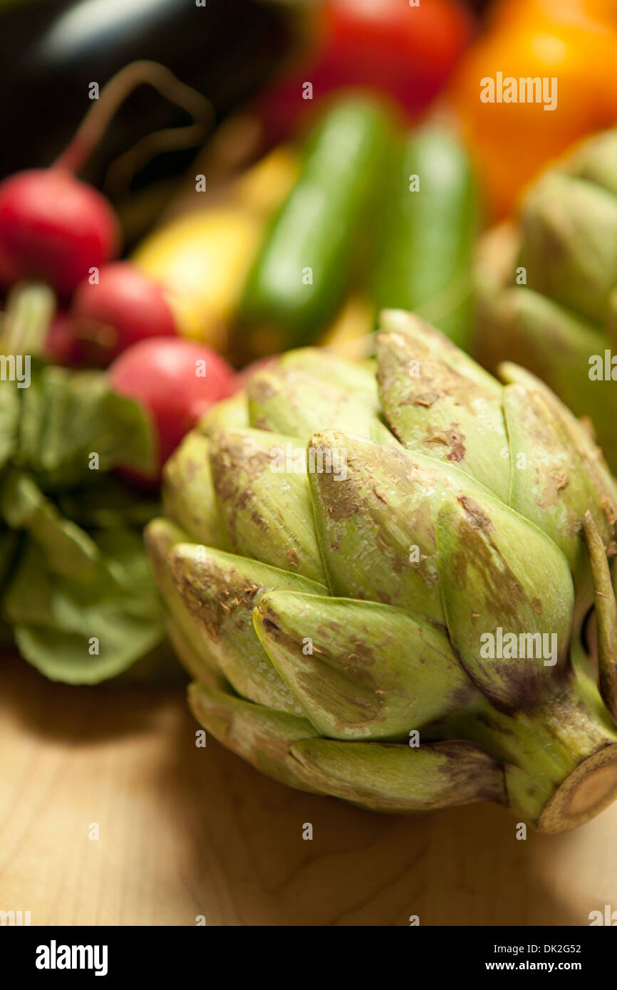 Close up high angle view of organic artichoke and variety of vegetables on cutting board - Stock Image