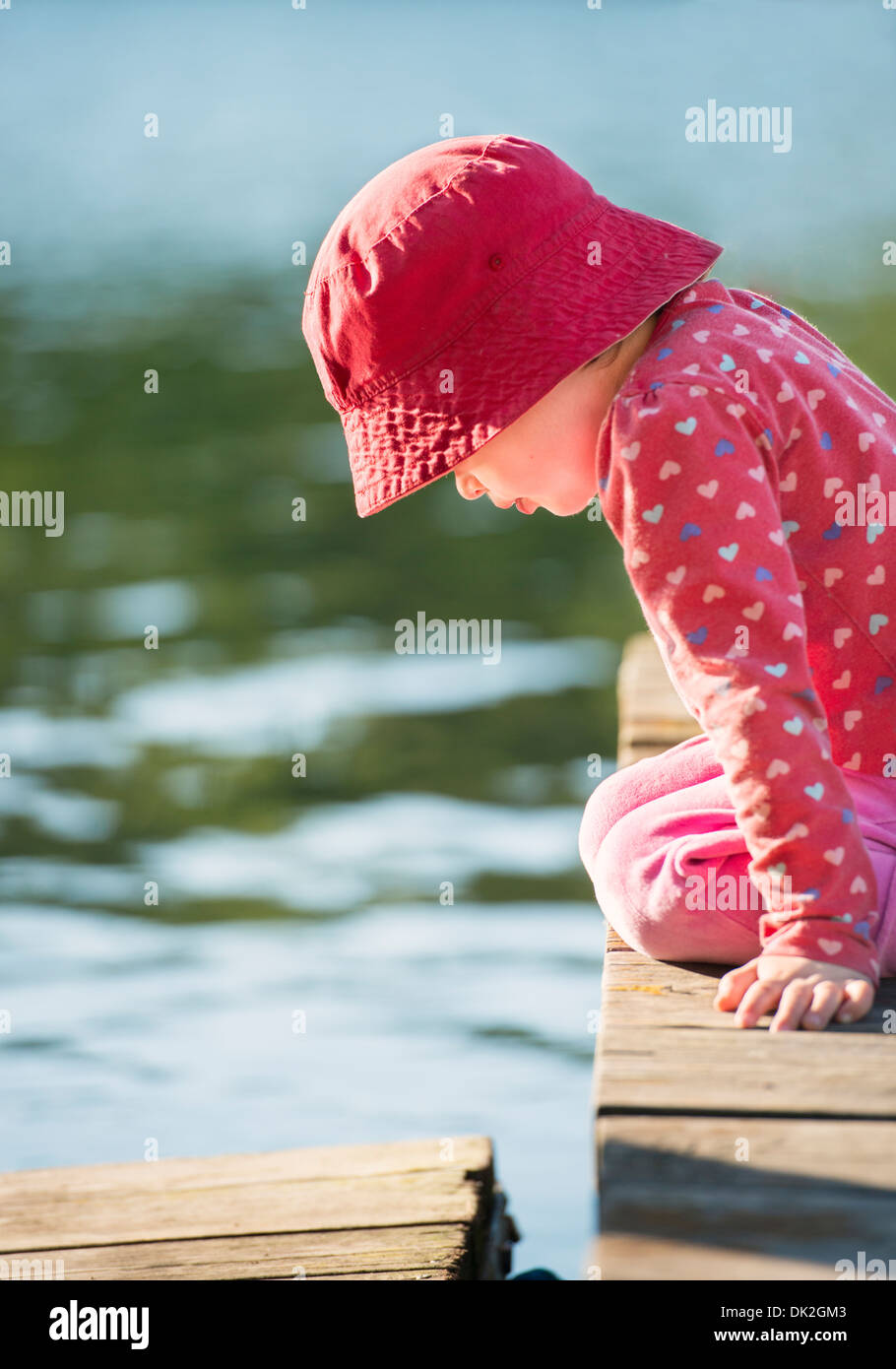 Lifestyle moment of summer childhood. Little girl sitting on jetty, looking down. - Stock Image