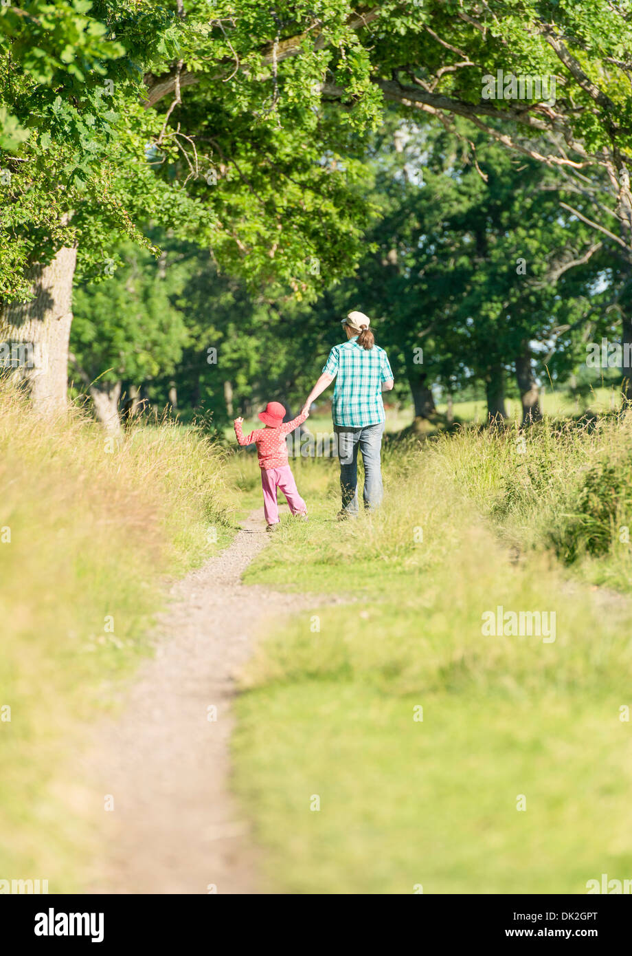 Little girl and woman walking in green summer landscape, Sweden - Stock Image
