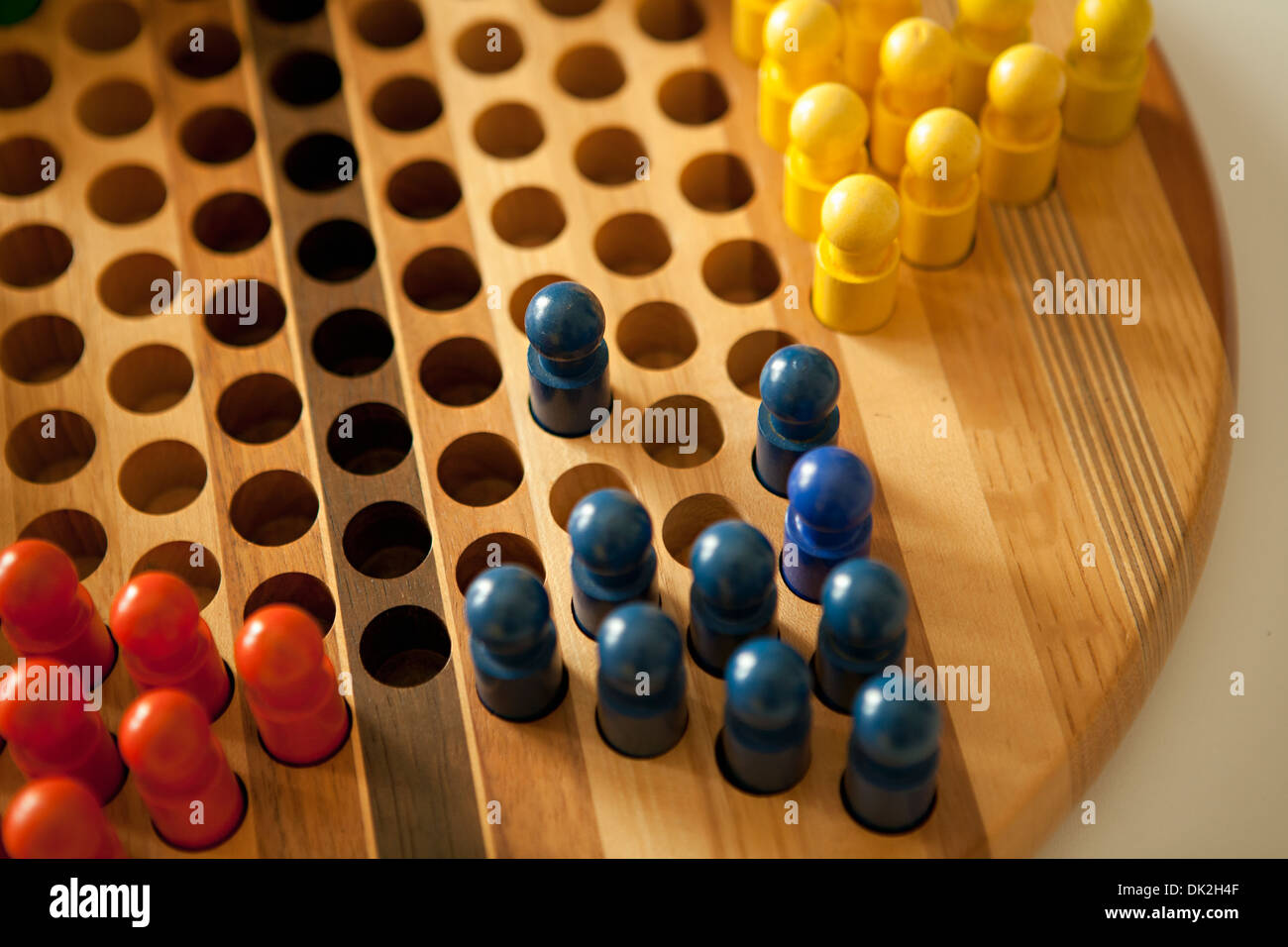Close up high angle view of colored pegs in Chinese checkers board - Stock Image