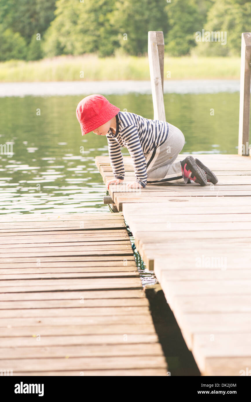 Lifestyle moment of summer childhood. Little girl playing on jetty, Sweden - Stock Image