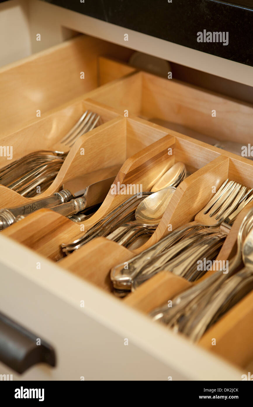Close up high angle view of open organized silverware drawer - Stock Image