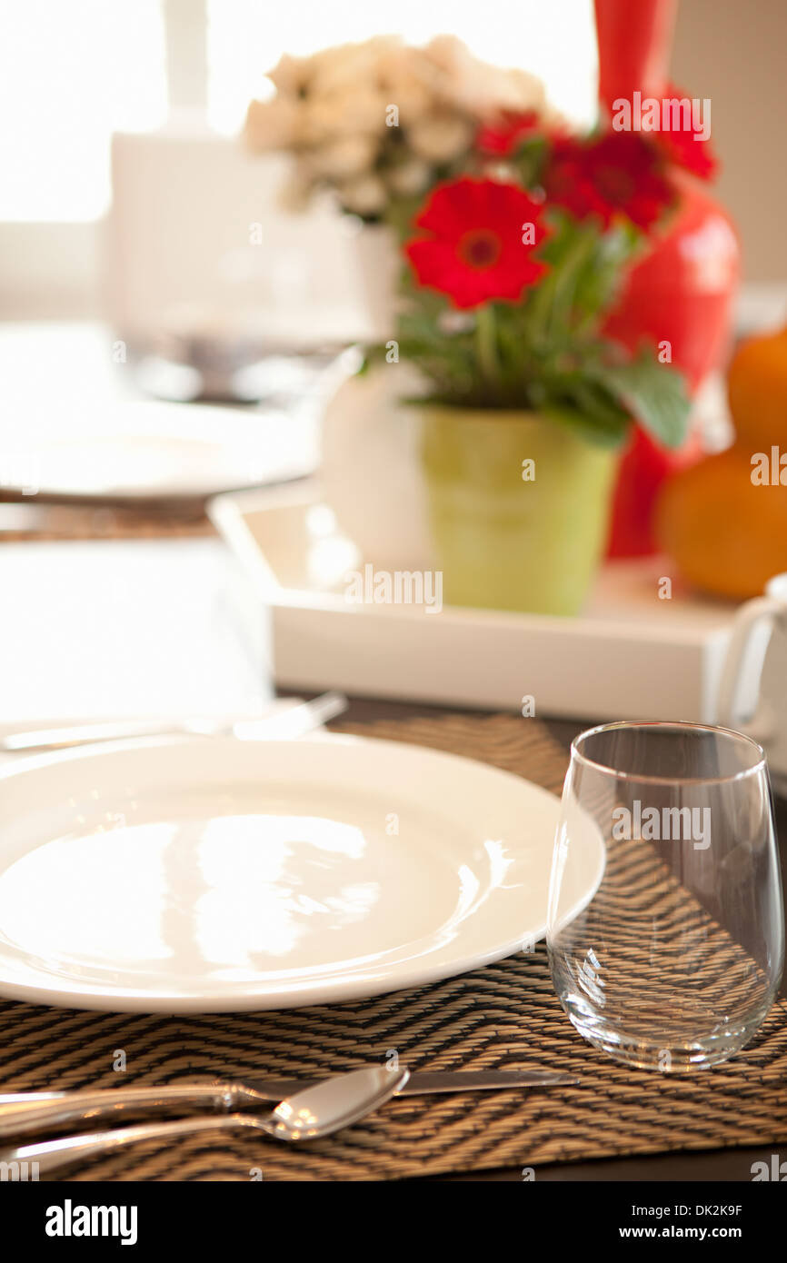 Close up of place setting on dining table with flower arrangement - Stock Image