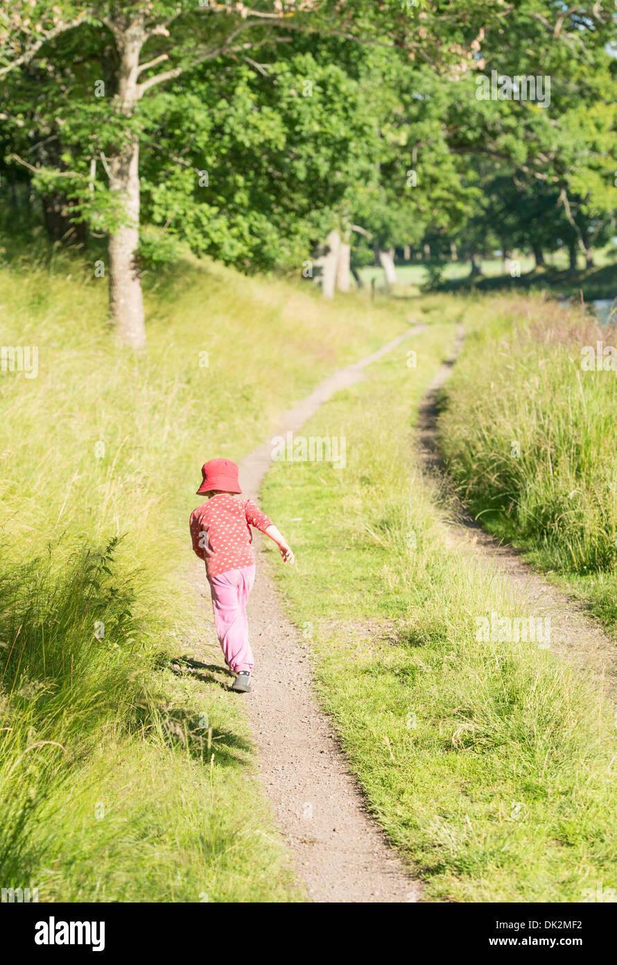 Little girl running on dirt road in green summer landscape, Sweden - Stock Image