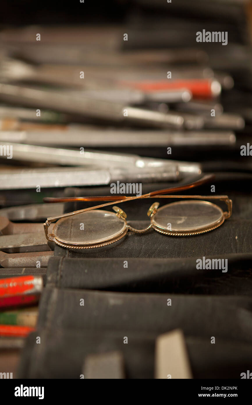 Close up of eyeglasses on sculptor's table with creative tools - Stock Image