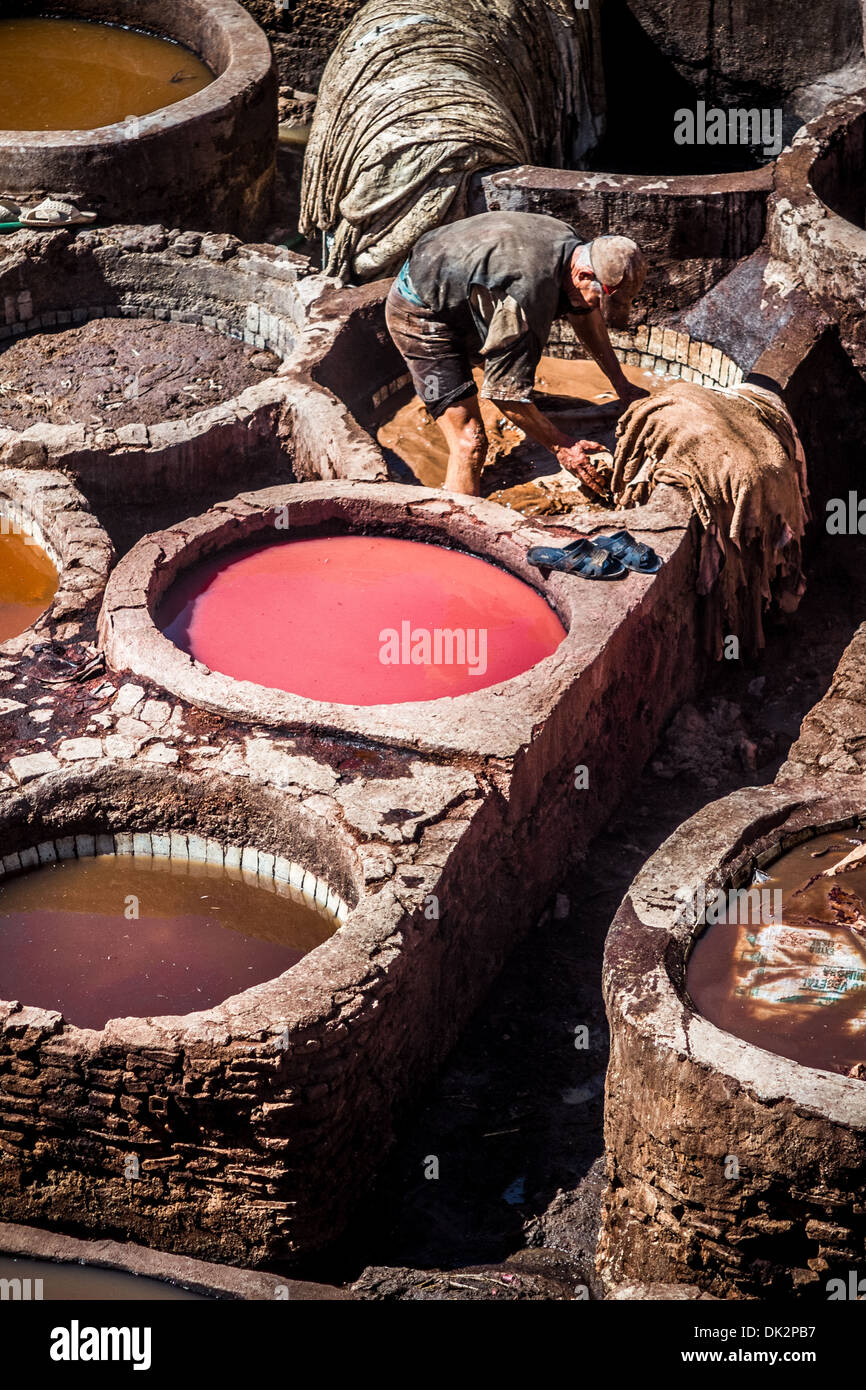 Tanners working leather in the old tannery of Fes, Morocco - Stock Image