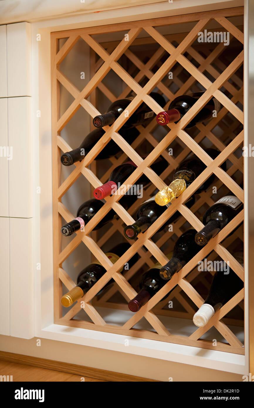Wine bottles in built-in wooden wine rack - Stock Image