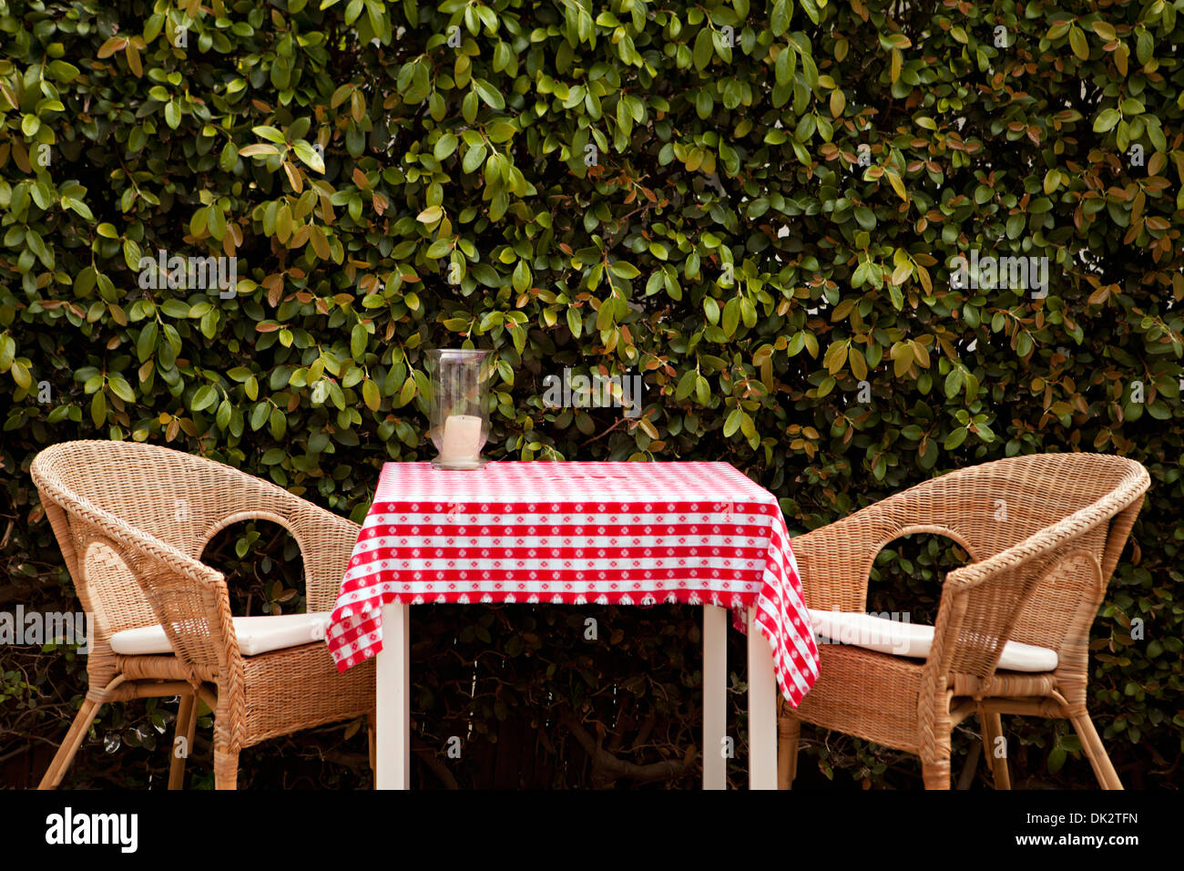 Wicker chairs at patio table with red and white tablecloth - Stock Image