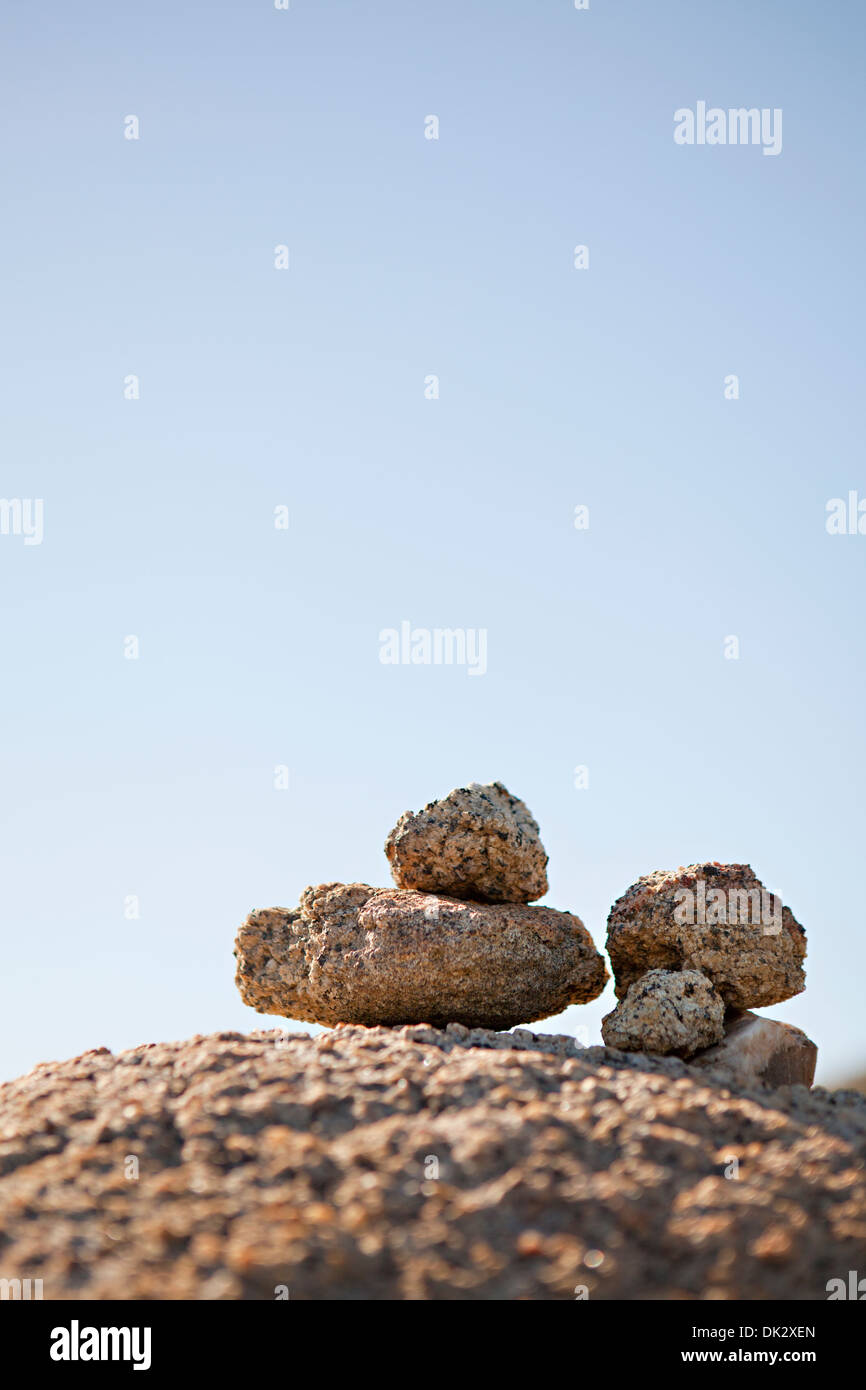 Stacked zen-like stones against sunny blue sky - Stock Image