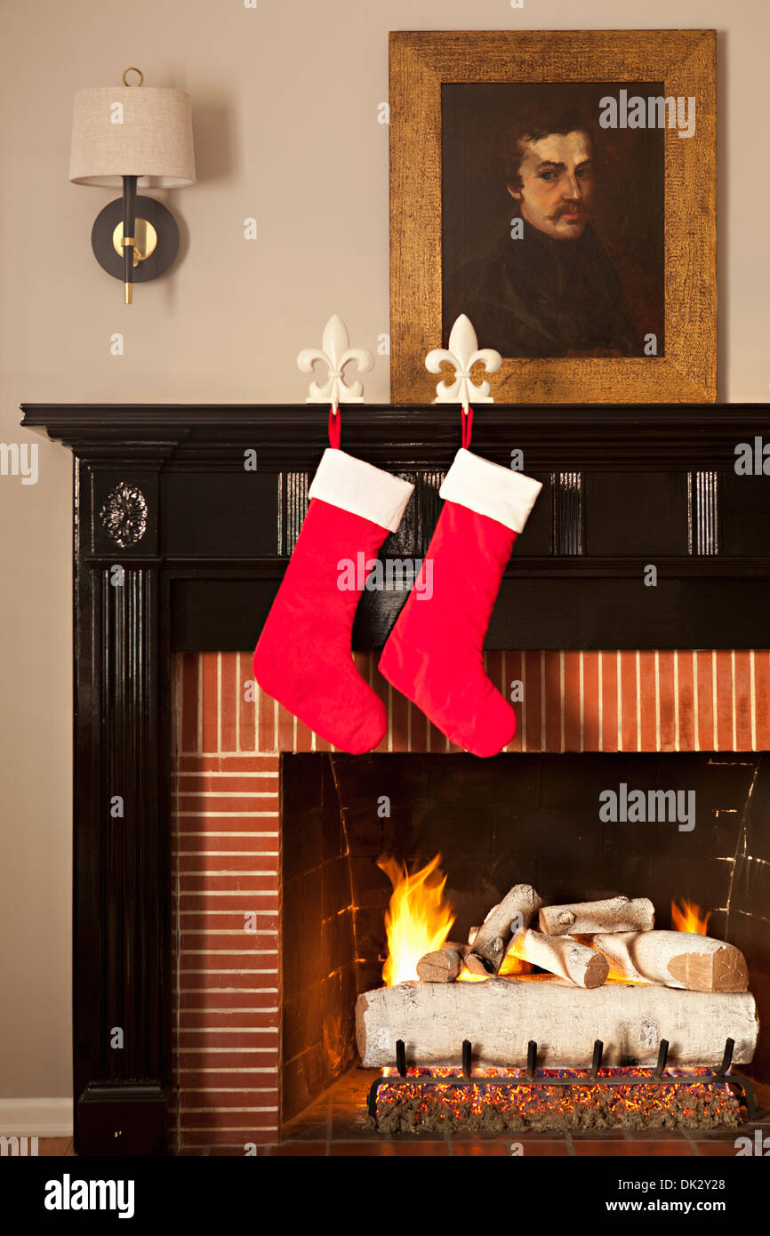 Christmas stockings hanging from fleur-de-lis holders on fireplace - Stock Image