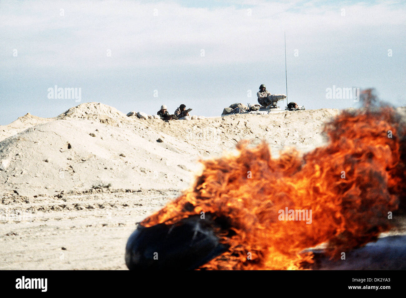Armored units wait along a sand berm as destroyed vehicles burn during Operation Desert Storm February 28, 1991 in Kuwait. - Stock Image